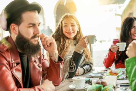 Happy hipster people drinking cappuccino and eating muffins - Young friends toasting coffee and doing breakfast in bar restaurant bakery shop - Friendship concept - Focus on left girl - Warm filter