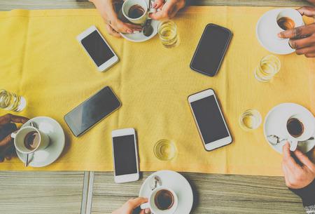 Widok z góry na ręce znajomych, opiekanie wloskiego stylu kawy w barze kawiarnia restauracja - różnorodna kultura osób picie espresso w kafeterii - uzależnienie od kofeina i technologii - ciepły filtr matowy