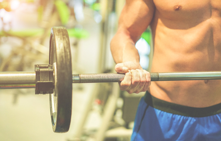 Atleta de levantamiento de peso en el club de gimnasio americano con entrenador personal - Hombre joven haciendo entrenamiento de fuerza - Concepto de fitness, concentración y culturista - Enfoque en la mano del hombre - Cine filtro cinematográfico