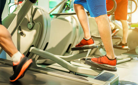 Group of people training on tapis roulant inside gym club - Fitness man running and using eliptical cross trainer - Wellness and body building concept - Focus on center man left foot - Warm filter