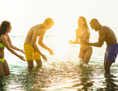 Happy friends having fun inside water for after sunrise party in ibiza - Yong people enjoying summer holiday - Vacation and friendship concept - Focus on center silhouette guys - Warm filter Stock Photo