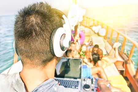 Wielorasowe młodzi przyjaciele o imprezie łodzią na zachodzie słońca - Dj odtwarzanie muzyki z rozmytych ludzi w tle - Koncepcja nowych trendów muzycznych - Nieostrość na prawym słuchawce - Ciepły filtr z promieniami słońca halo