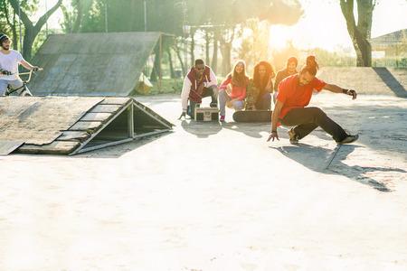 Grupo de amigos felices escuchando música y viendo breakdancer perfoming en el parque de skate de la ciudad - Los jóvenes que se divierten - Hip hop concepto de estilo de vida - Enfoque en el hombre bailando - Filtro caliente con luz solar Foto de archivo