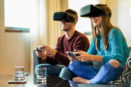 Jóvenes felices pareja jugando videojuegos realidad virtual gafas en su apartamento - Alegre personas se divierten con nuevas tendencias tecnología - Concepto de juego - Suave enfoque en la mujer frente auriculares