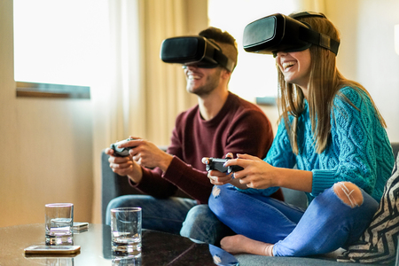 Young happy couple playing video games virtual reality glasses in their apartament - Cheerful people having fun with new trends technology - Gaming concept - Soft focus on woman front headset