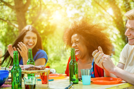 Happy friends having barbecue meal outdoor with back sun light - Young people having at bbq party toasting beers - Friendship,summer and dinner concept - Focus on right man face - Warm filter Foto de archivo