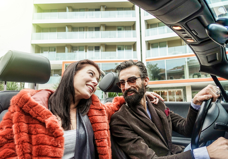 Hipster happy couple smiling inside cabriolet car during business trip - Fashion people having fun together - Business and trendy fashion concept - Warm vintage filter with sun halo flare