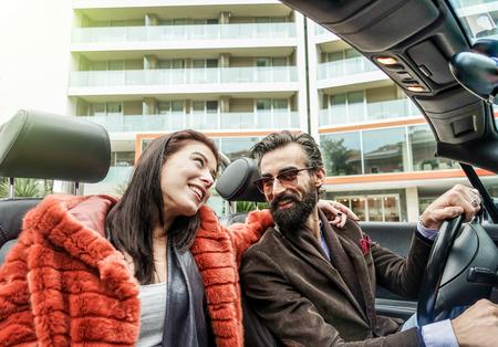 Hipster szczęśliwej pary uśmiecha się wewnątrz samochodu kabriolet podczas podróży służbowej - ludzie mody zabawy razem - koncepcja mody i mody - ciepłe zabytkowe filtra z sun flames halo