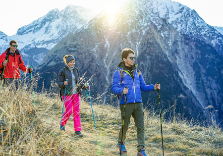 Three trekkers doing excursion on alps top french mountain - Young happy people hiking with back sun light - Sport,healthy lifestyle and recreation concept - Focus on right man - Warm filter