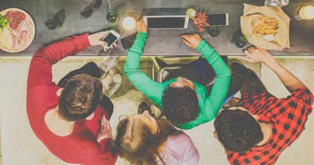 Pohled shora na kamarády, kteří sledují videa v tabletách a opírají se o pivo v hospodě vinářských pivovarů - Mladí lidé se baví s technologií nových trendů na břidlicovém pultu - Zaměřili se na ruce v tabletu - Teplý matný filtr