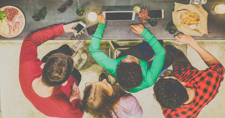 Top view of friends watching videos in tablet and toasting beer in winery brewery pub - Young people having fun with new trends technology on slate counter - Focus on tablet hands - Warm matte filter Stock Photo