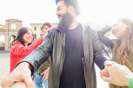 Jóvenes amigos divertirse en la ciudad Viejo centro de la ciudad con la luz de fondo - Grupo de gente feliz alegre sonriendo y jugando al aire libre - Amistad y concepto de la juventud - Filtro caliente - Centrarse en el hombre barbudo