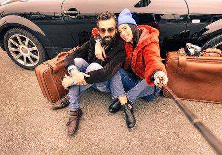 Hipster couple making selfie with stick  - Travel and fashion lifestyle concept  - Brown vintage filtered look Foto de archivo
