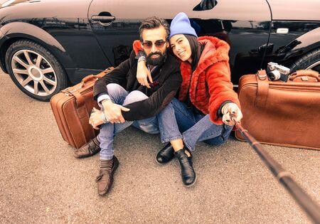 Hipster pareja haciendo selfie con palo - Viajes y moda concepto de estilo de vida - Brown vintage filtrado mirada