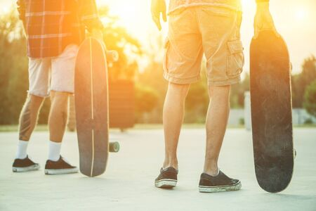 Skaters friends outdoor in urban city with skateboards in their hands - Young people training longboard extreme sport - Friendship concept - Soft focus on right mans hand holding board - Warm filter Stock Photo