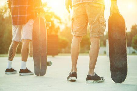 Znajomi z łyżwiarstwa na świeżym powietrzu w mieście z deskorolkami w rękach - Młodzi ludzie trenują longboard ekstremalny sport - Przyjaźń koncepcji - Miękkie fokus na prawym ręka mężczyzny trzyma deskę - Ciepły filtr