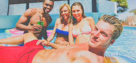 Multi ethnic couples doing party in swimming pool - People making selfie in summer vacation - Young friends having fun toasting cocktails - Holidays concept - Focus on right man - Warm matte filter