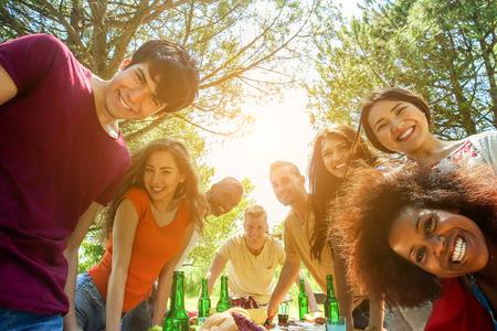 Estudiantes amigos tomando selfie al aire libre en la comida de barbacoa - Concepto de joven feliz con los jóvenes que se divierten juntos - Concepto de humor positivo - enfoque suave en afro pelo de la cara de la niña pelo superior - Filtro caliente