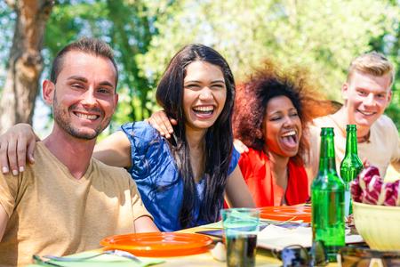 Multirracial grupo de amigos comiendo y disfrutando de barbacoa comida de verano partido - Los jóvenes que se divierten en el parque al aire libre - Centrarse en izquierda guy - Felicidad con el concepto de alimentos - Vivid cruz procesado filtro