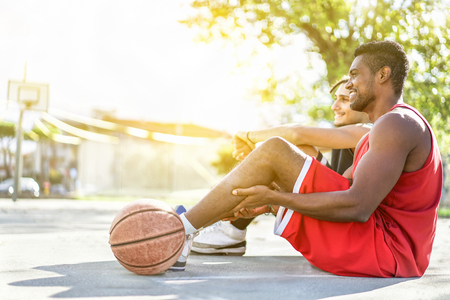 Two cheerful basketball players sitting on urban city basket camp with back light - Multiracial friends relaxing and chilling after played sport match - Sport and school concept - Warm filter