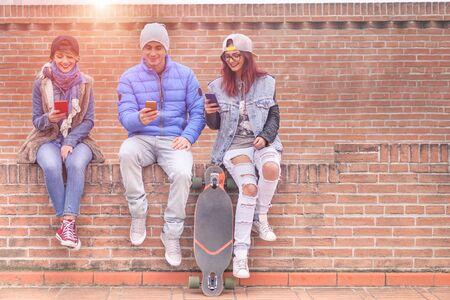 Skupina mladých přátel, kteří hrají online s chytrými telefony venkovní - Šťastní trendoví lidé jsou závislý na mobilu - Technologie a módní koncepce v městské soutěži - Teplý filtr s umělým slunečním světlem