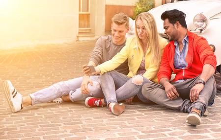 Multiracial amis heureux prenant un selfie assis à la prochaine vieille voiture vintage - Les gens heureux s'amusent à l'aide d'un téléphone cellulaire - Concept international du bonheur et de l'amitié multi-ethnique - Focus sur la fille blonde