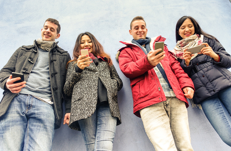 Skupina mladých přátel hledá jejich smartphony v centru starého města - Technologie a koncepce sociální sítě - Teplý filtr Reklamní fotografie