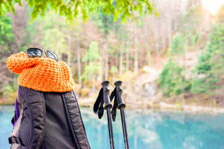Trekking equipment with blue lake and mountain forest in background on the top at sunrise - Hiking and healthy lifestyle concept - Focus on knit hat and backpack - Warm vivid filter