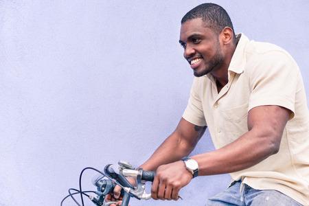 행복 한 흑인 남자 승마 오래 된 스타일 자전거 야외 -Hipster 흑인 남자 재미 - 건강 한 라이프 스타일과 행복 개념 - 따뜻한 빈티지 필터링 된 봐 - 얼굴