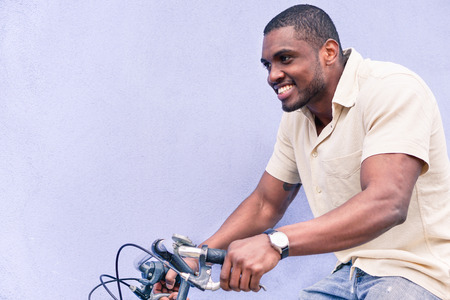 A happy African American man riding old style bicycle outdoor - Hipster black guy having fun - Healthy lifestyle and happiness concept - Warm vintage filtered look - Focus on face Foto de archivo