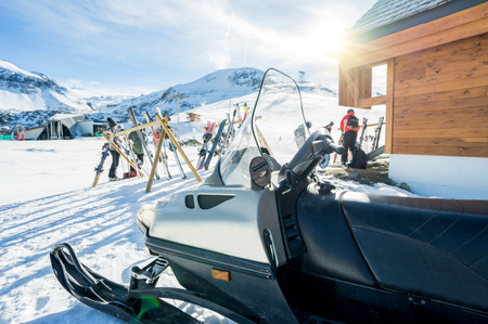 View of winter snow vacation resort - Ski,snowboards and snowmobile outside of mountain bar restaurant with back sun light - Holidays and sport concept - Warm vivid filter - Focus on snowmobile