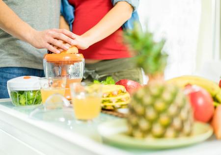 과일과 야채 - 임신 아내와 영양에 대한 돌보는 그녀의 남편과 건강 채식주의 아침을 준비하는 젊은 부부 - 건강과 가족 개념 - 사람 손에 초점 - 따뜻한