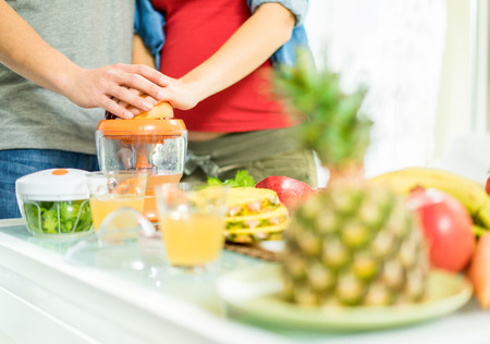 Young couple preparing healthy vegetarian breakfast with fruits and vegetables - Pregnant wife and her husband taking care about nutrition - Health and family concept - Focus on man hand - Warm filter Foto de archivo