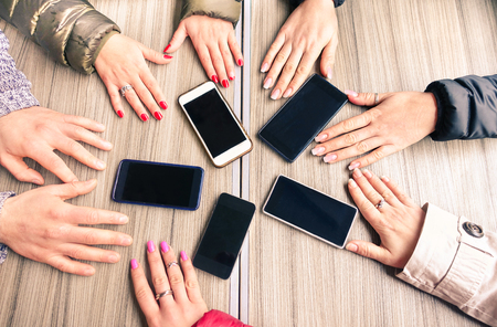 Group of friends having fun together with smartphones - Closeup of hands social networking with mobile cellphones - Technology and phone addiction concept on wood background - Focus on mobile phones