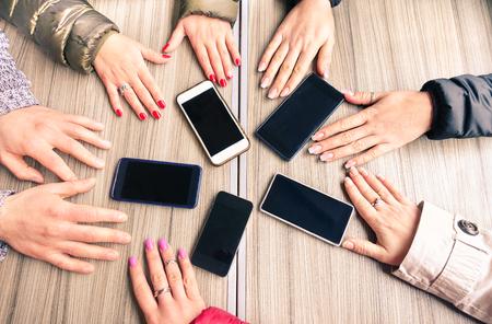 Grupa przyjaciół zabawę razem z smartfonów - zbliżenie rąk sieci społecznych z telefonów komórkowych - Koncepcja technologii i uzależnienia od telefonu na tle drewna - skoncentrowanie się na telefonach komórkowych