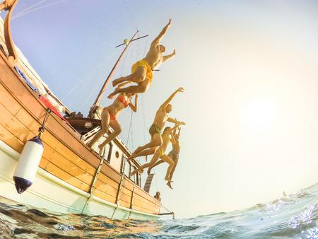 Šťastní přátelé potápění z plachetnice do moře - Mladí lidé baví v letní party den skákání v oceánu - Dovolená a přátelství koncepce - Měkké zaměření na levého muže - Fisheye sklo zkreslení