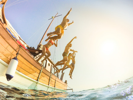 Happy friends diving from sailing boat into the sea - Young people having fun in summer party day jumping in ocean - Vacation and friendship concept - Soft focus on left man - Fisheye lens distortion