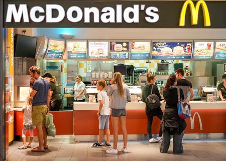 CAGLIARI, ITALIA - 18 DE OCTUBRE DE 2016: interior del restaurante McDonald's. McDonald's es la cadena más grande del mundo de restaurantes de comida rápida de hamburguesas, fundada en los Estados Unidos - Suave enfoque en la gente