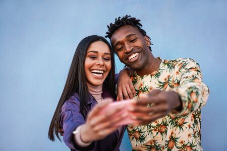 Latin couple doing photos and videos for social media - Young people having fun with new trend technology - Love, fashion and relationship concept - Focus on faces