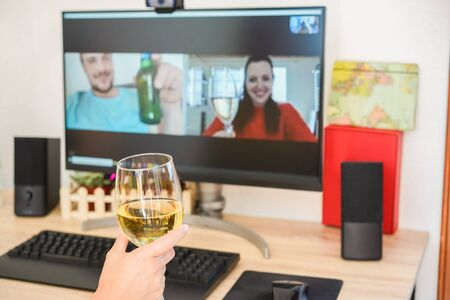 Young woman chatting and drinking wine on computer meeting room with friends - Alternative party during stay sahe at home and isolation quarantine - Focus on glass