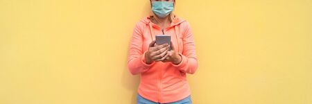Young woman using smart mobile phone app outdoor while face protection wearing mask during Covid-19 time - Concept of youth, tech, prevention and outbreak - Focus on hands