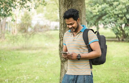 Young indian man using smartphone app in university campis - Happy asian guy having fun watching videos on mobile cell phone - Technology and millennial generation concept - Focus on his face Stock Photo