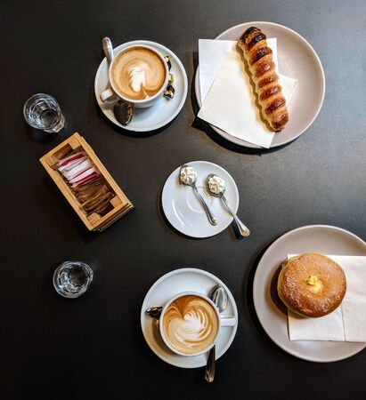 Italian breakfast for two (from above) on a black table. Two Cappuccino, a Cannoli, a Krapfen (Italian doughnut) two small glasses of sparkling water and two spoons of whipped cream