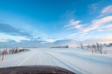 Road trip in the Arctic on a snow covered ice road with car hood / bonnet visible at the bottom of the frame
