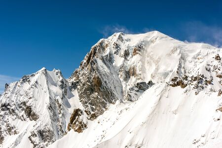 Snow covered rocky mountain peak with wind blowing off the snow from the top into a clear blue sky Reklamní fotografie