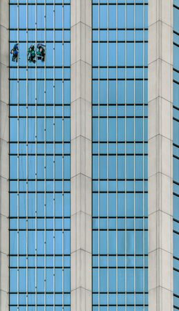 Window washers working at height on the glass facade of a skyscraper