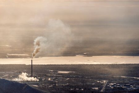 Mining industrial complex with chimney spewing smoke in a forest next to a frozen river in an otherwise pristine environment - horizontal