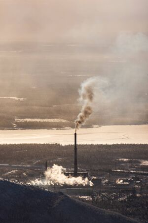 Mining industrial complex with chimney spewing smoke in a forest next to a frozen river in an otherwise pristine environment - vertical Reklamní fotografie