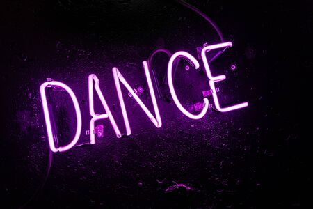 Purple neon light creating the word DANCE on a black wall in a disco or night club