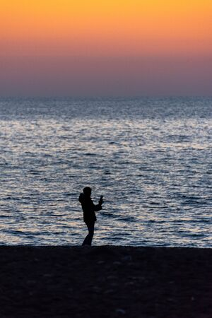 Silhouette of person holding a smartphone in front of the sea at sunset Stok Fotoğraf